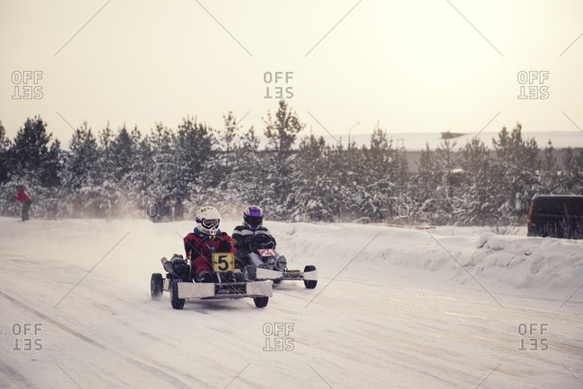Go-kart drivers on a snowy track