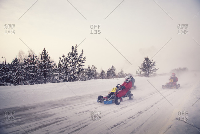 Three drivers racing go-karts on a snow covered track