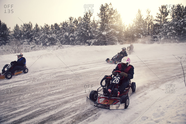 Go-kart racers round a bend on a snowy track