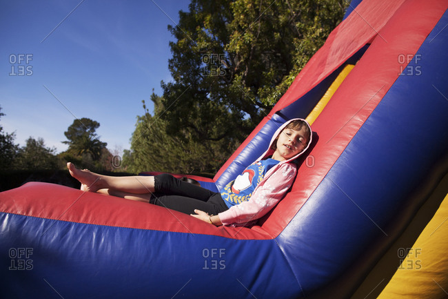 Young girl relaxing in the sun on a bounce house