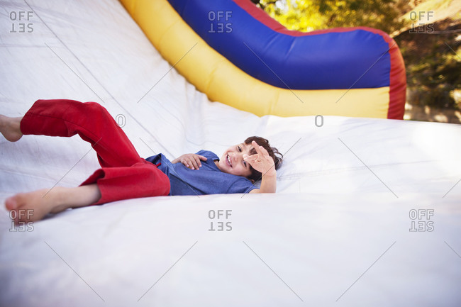Child lying at the base of an inflatable slide