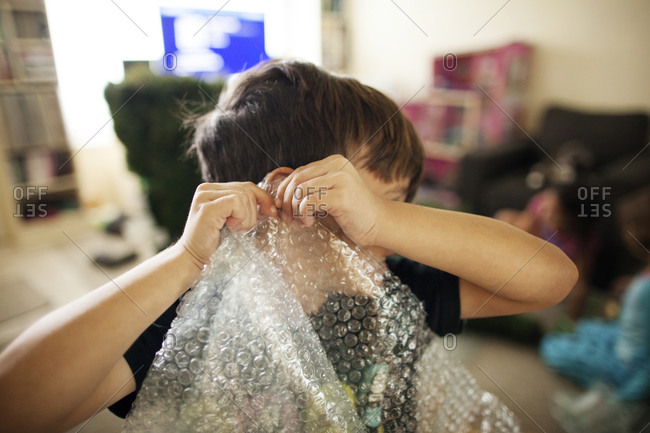 Boy listening to sound while popping bubble wrap