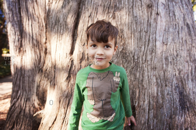 Boy in humorous bigfoot shirt stands against a huge tree trunk