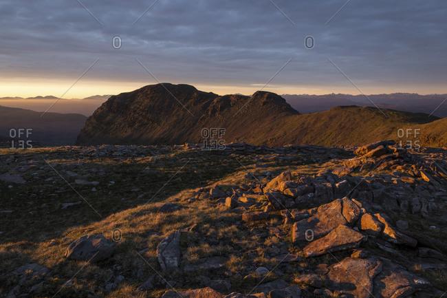 Landscape of barren hills at sunset