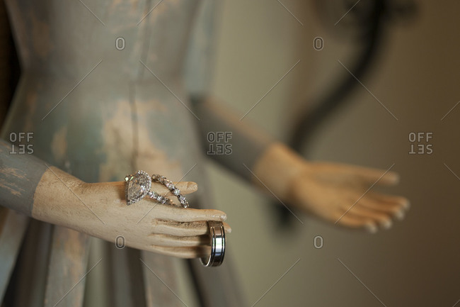 Wedding bands hanging on hands of wooden statue
