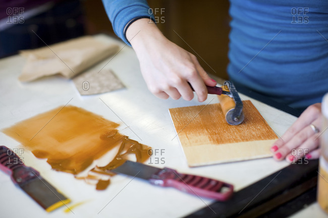 Woman painting a piece of wood with a roller