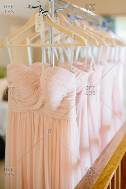 Dresses of the bridesmaids hanging on a rack