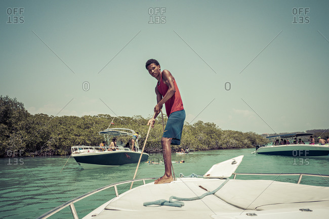 Cartagena, Colombia - April 22, 2015: Boy guiding boat in Caribbean sea in Colombia