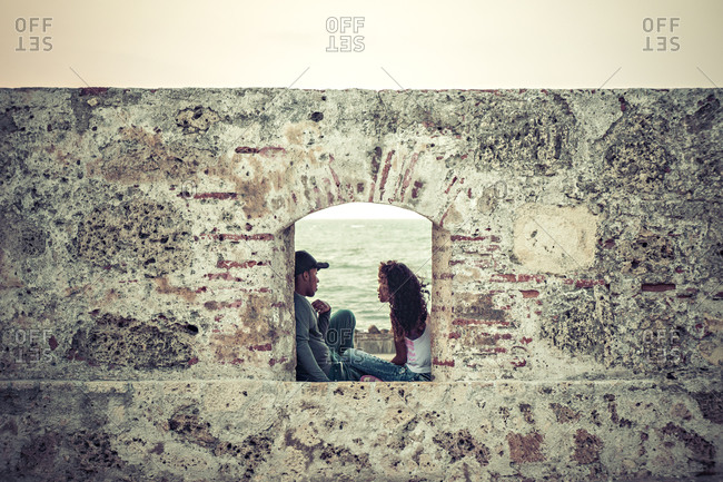 Cartagena, Colombia - April 7, 2015: Couple talking on city wall in Cartagena, Colombia