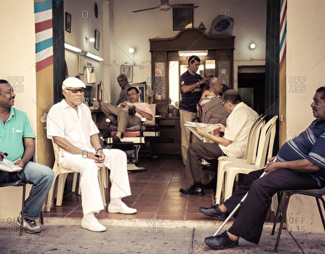 Cartagena, Colombia - April 24, 2015: Men gather at barbershop in Cartagena, Colombia