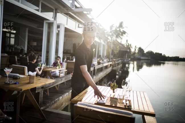 Ho Chi Minh City, Vietnam - February 25, 2015: Waiter setting table at restaurant on  Saigon River in Ho Chi Minh City, Vietnam