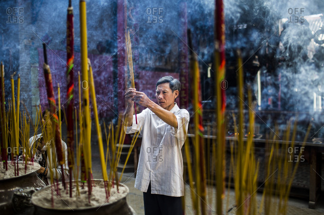 Ho Chi Minh City, Vietnam - February 26, 2015: Man lights incense and prays at pagoda in Ho Chi Minh City, Vietnam