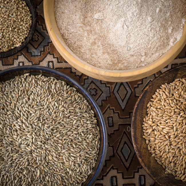 Bowls of spelt grains, rye grains, buckwheat grains, whole grain and wheat flour