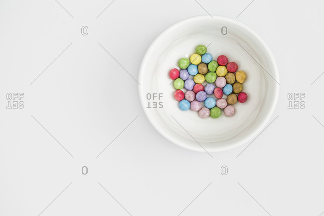 Pastel colored sweets in a white bowl on white background