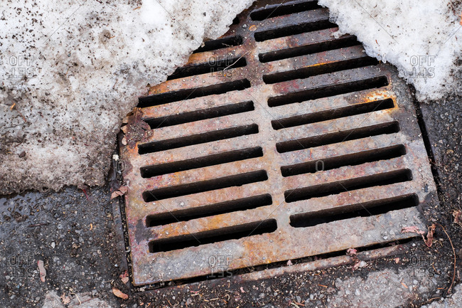 Metal grid drain in street partially obscured by snow