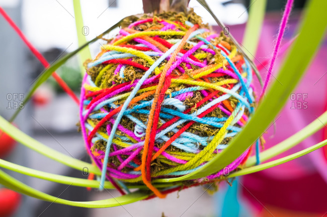 Colorful ball of yarn with strings coming out of it