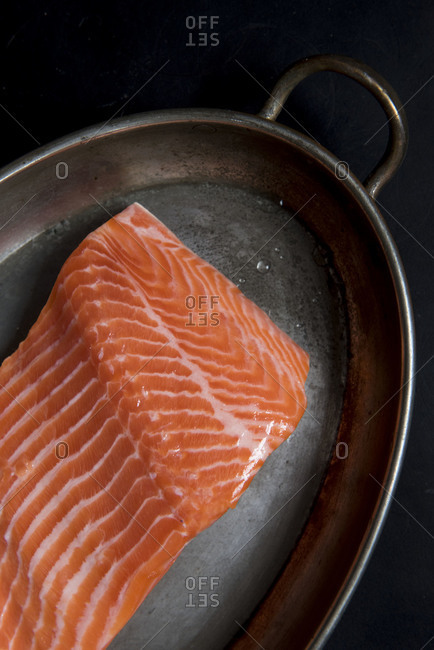 A filet of fresh salmon in a roasting pan