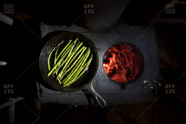 A pan of asparagus being cooked on a wood stove