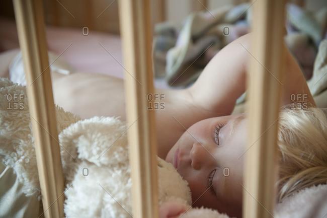 A blonde boy asleep in a crib