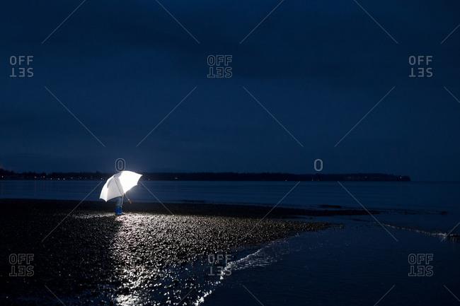 A man holds an umbrella at night
