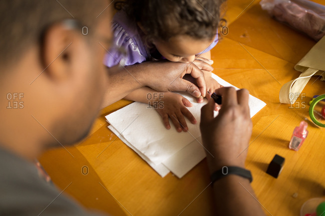 A father helps his daughter paint her nails