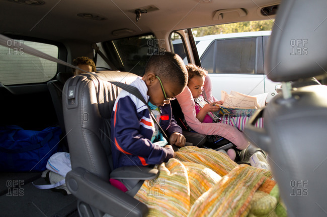 Three children get buckled into their car seats