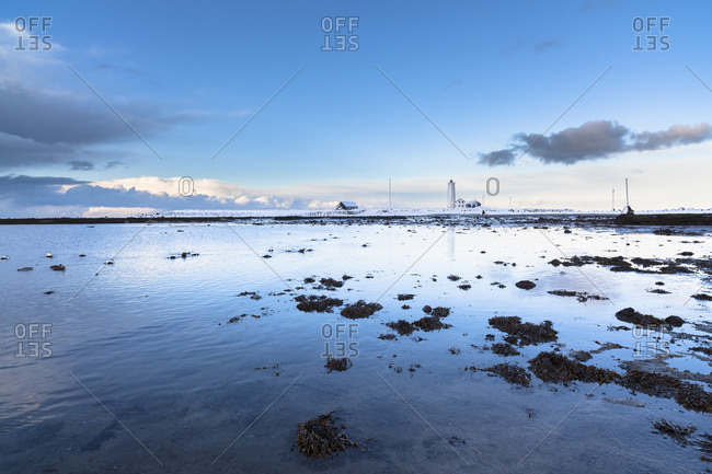 Blue sky reflected in shallow water and snow-covered Seltajarnarnes