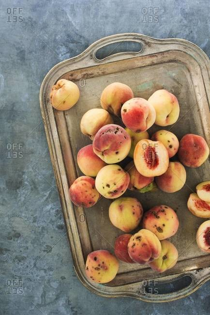 Overhead view of mottled peaches on a silver tray