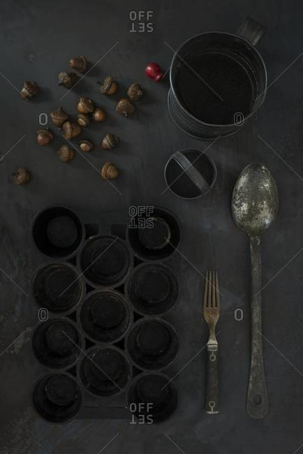 Overhead view of antique popover pan and acorns