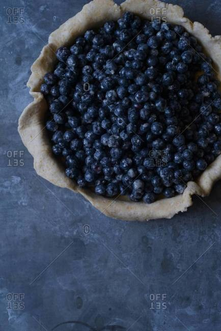 Overhead of a pie shell filled with blueberries