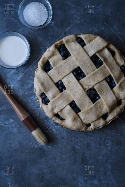 Finished lattice crust on blueberry pie with pastry brush, cream, and sugar