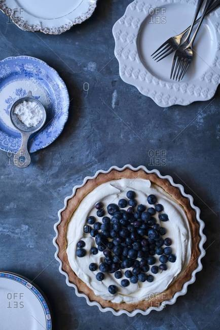 Overhead of a cream pie topped with blueberries