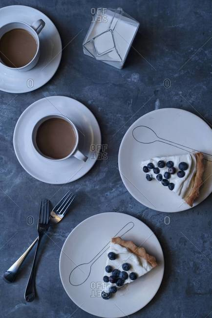 Two slices of cream pie with blueberries and coffee