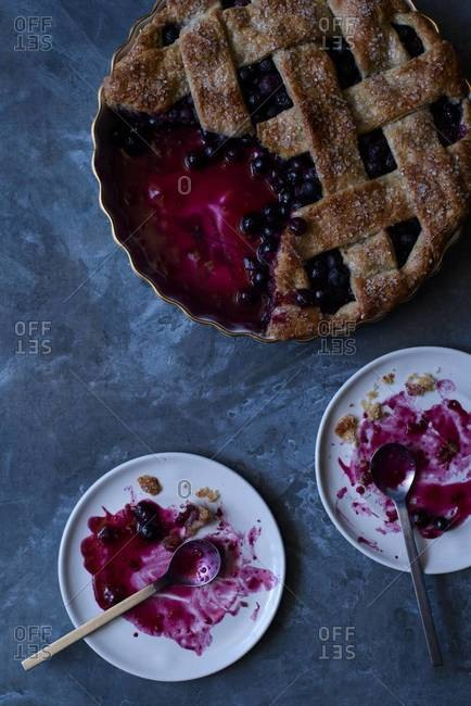 Overhead of a lattice crust blueberry pie with slices removed and serving remnants on plates
