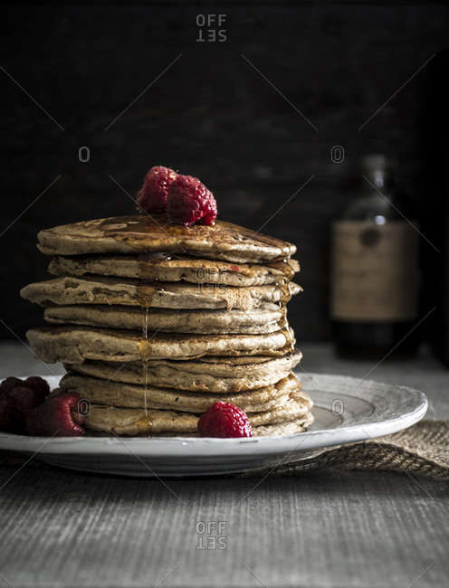 Raspberry pancakes with maple syrup served on a table