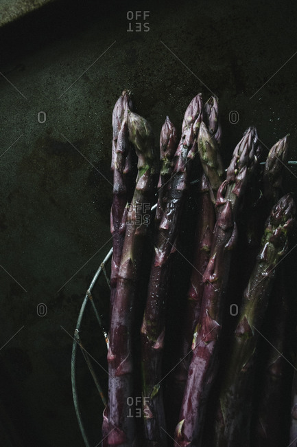 Purple asparagus stems on a baking sheet