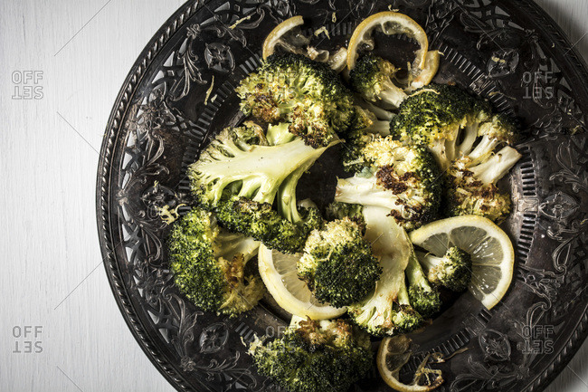 Roasted broccoli and lemon on a dark plate