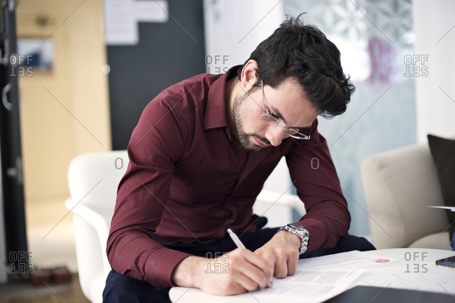 Man talking notes during meeting in office