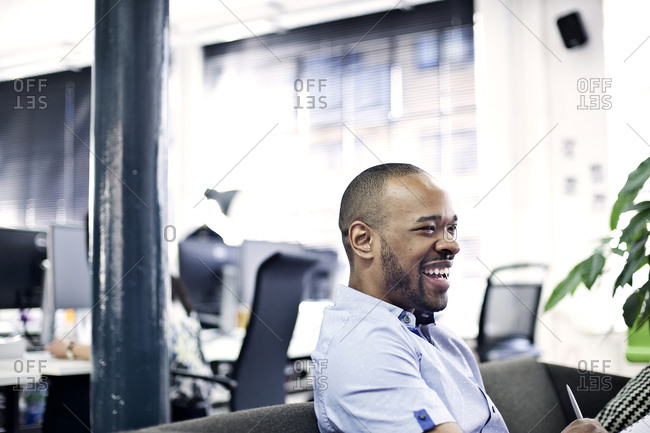 Man on couch laughing in office