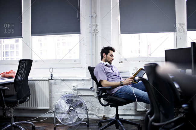 Man at office desk with tablet, headphones