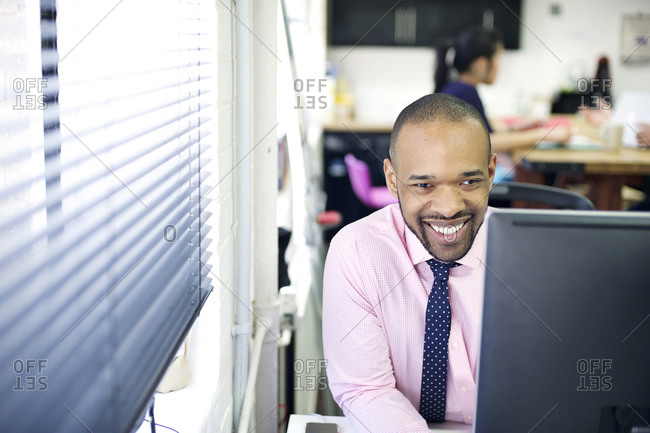 Man at his desk laughing in office