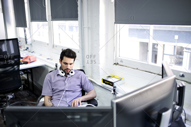 Man at office desk with book headphones