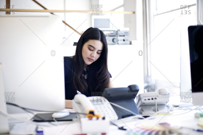 Woman concentrating on writing at desk