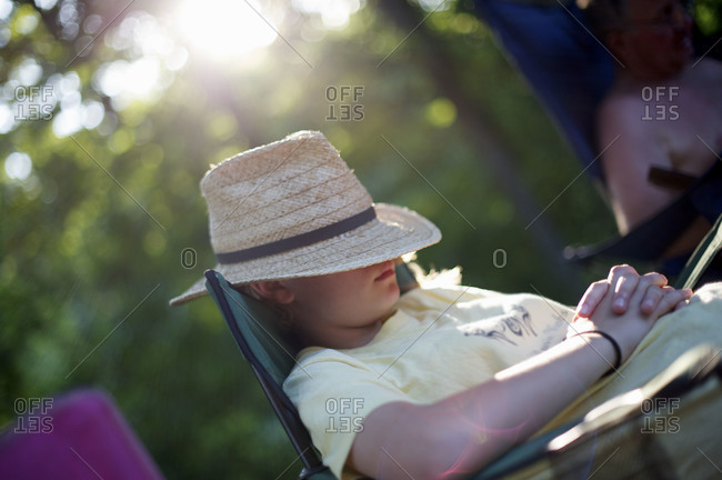 Young girl sleeping in a camping chair