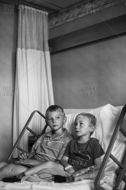 Boy sitting next to his sick brother in a hospital bed