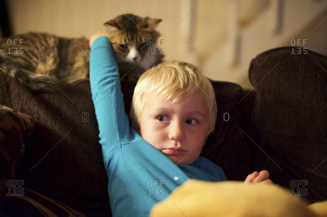 Boy petting a cat on the couch