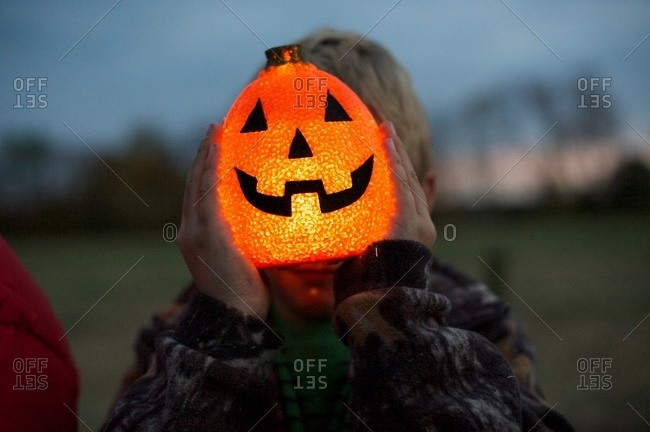 Boy holding a glowing pumpkin lantern in front of his face