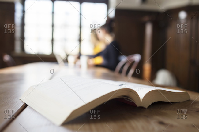Open textbook lying on cafe table with people in the background