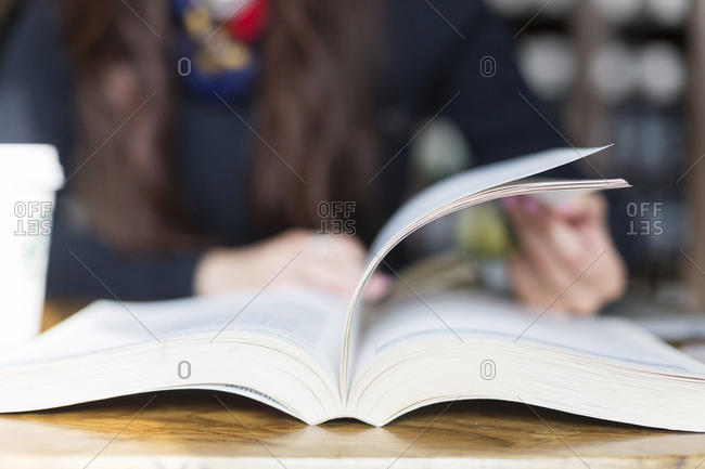 Close-up of student paging through a textbook