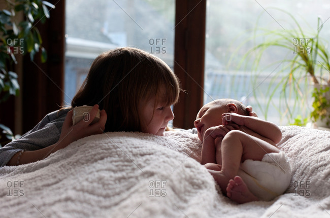 A little girl looks at her newborn baby sister